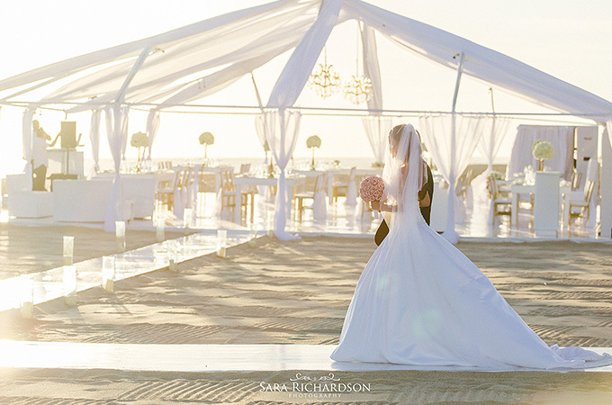bride walking on white path to white tent on beach