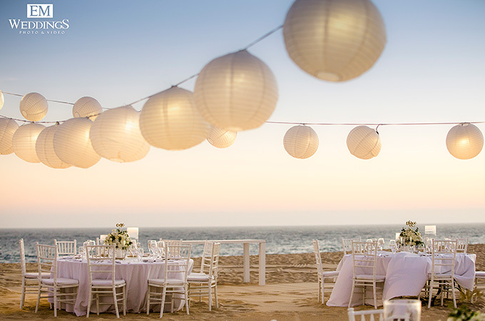 string lights of lanterns on beach with white tables