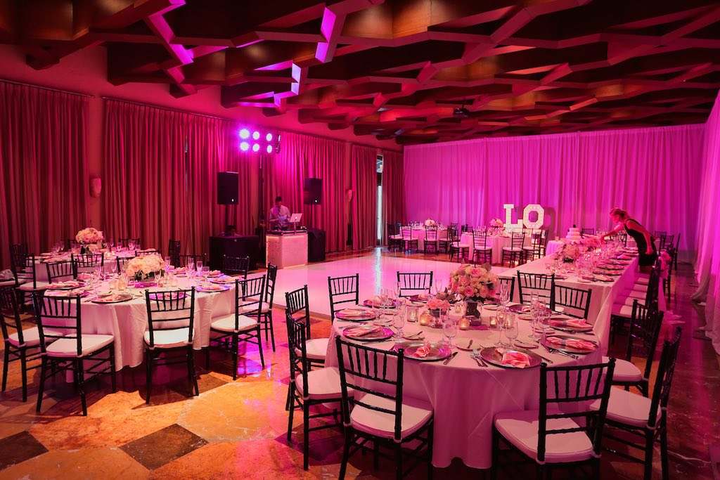 room with purple lighting, dance floor and tables