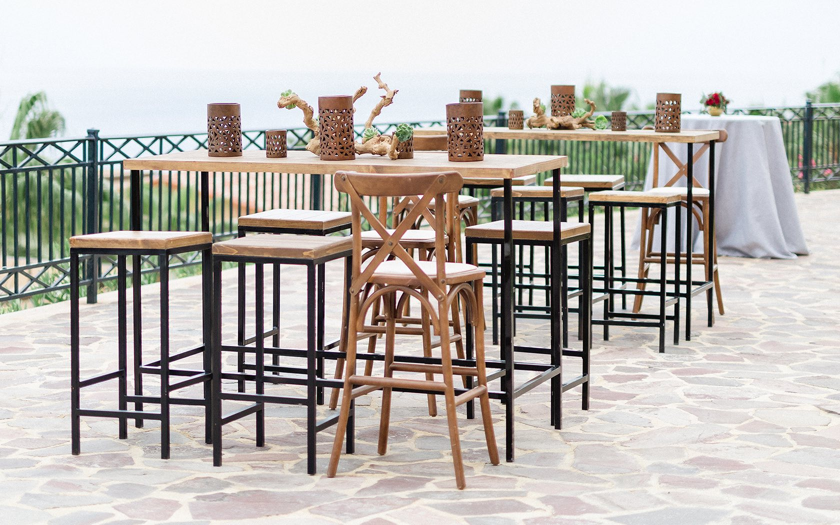 tall wooden table and chairs in outside venue
