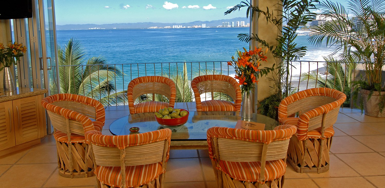 Living area with low round glass table & woven chairs with orange accents on balcony with ocean view
