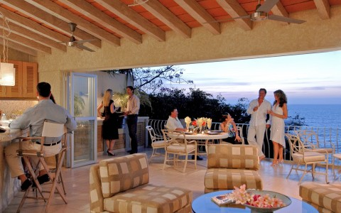 Social gathering in villa with open balcony overlooking sunset on ocean