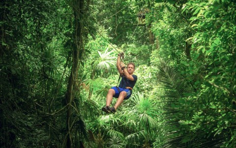 Man zip lining through jungle