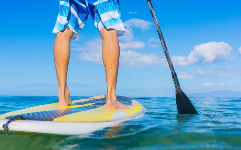 Close up of mans legs standing on paddle board rowing