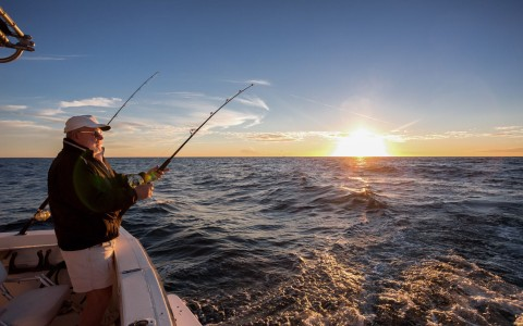Man fishing on boat during sunset