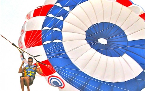 Man parasailing in sky