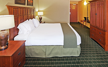 standard hotel room with king bed and white and green linens