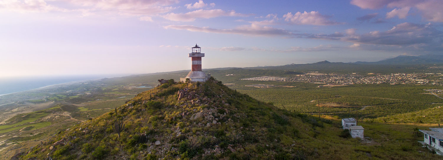 lighthouse on top of a mountain with the ocean in the background
