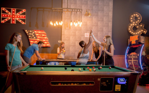 child and woman high fiveing while playing pool
