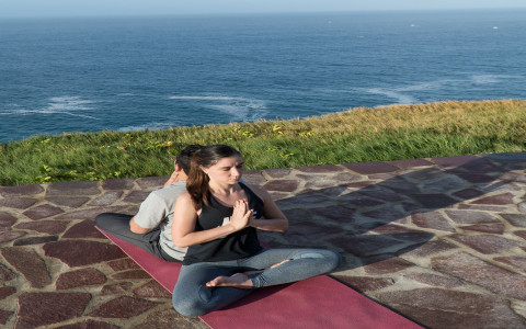 man and woman back to back in yoga pose on a cliff overlooking the ocean