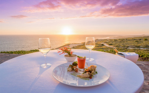 dinner on beach cliff during sunset