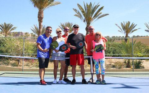 family holding paddle boards on tennis court