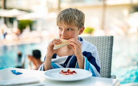 little boy eating a sandwich at the pool