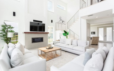 bright living room area with white couches and a chimney
