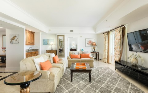 beige couches with orange accent pillows in a bright airy room