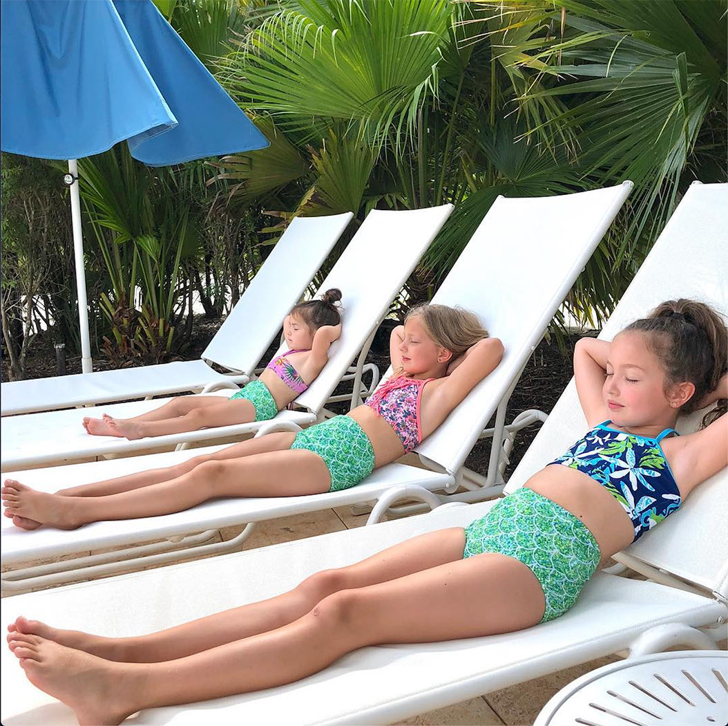 row of little kids sun tanning on pool chairs