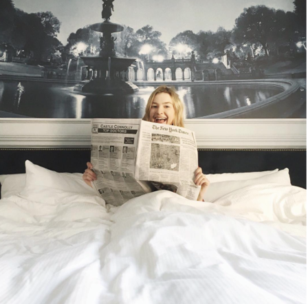 girl reading news paper in bed