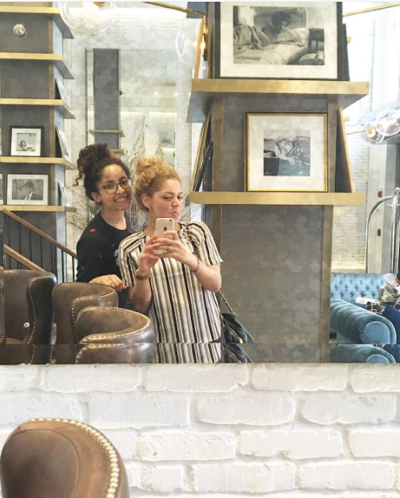 two girls taking a selfie in a mirror