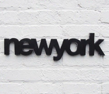 black new york letters on white brick wall