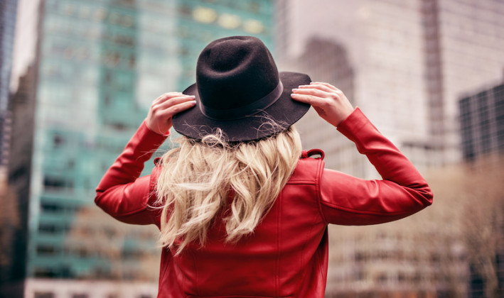 girl looking up from behind with blonde hair red leather jacket and felt hat