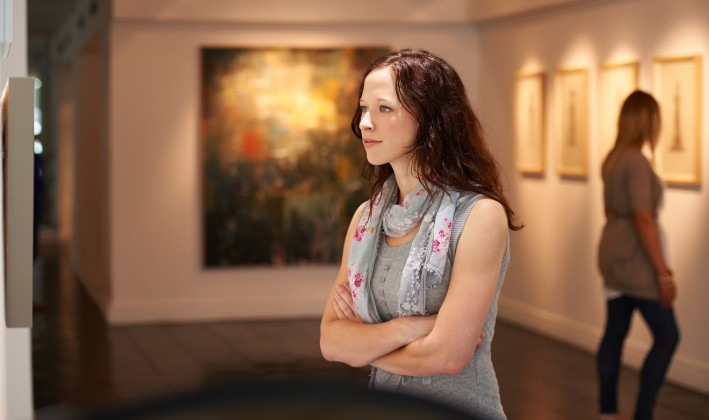 woman looking at art intensely in a museum or gallery