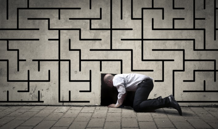 man crawling into a hole on a maze wall