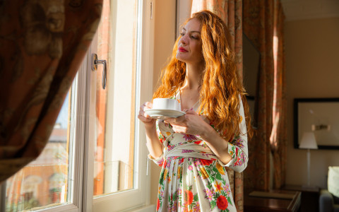 woman drinking coffee looking out the window