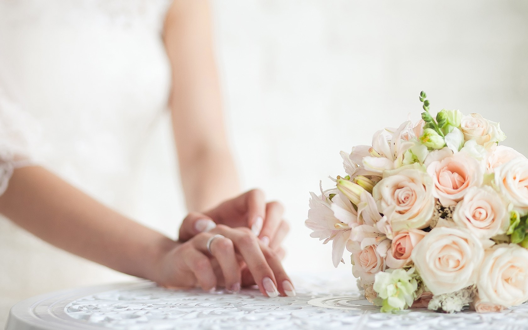 Close up of bride's hands next to flower bouquet