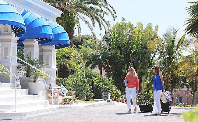 Two women with suitcases walking up to hotel entrance