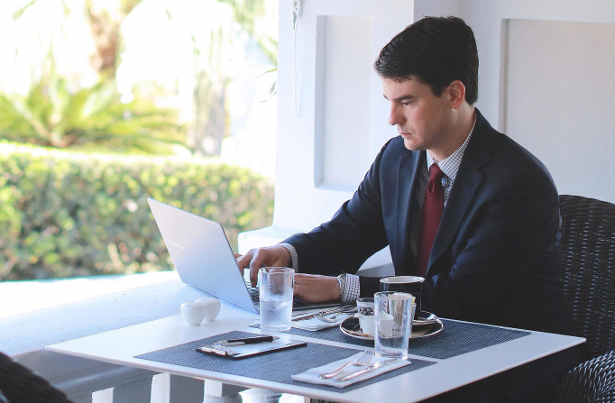 Businessman at outdoor terrace table with coffee & laptop