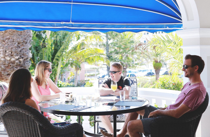 Group of friends sitting at round outdoor table with blue umbrella