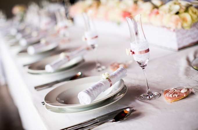 Close up of white rolled up handkerchief on white plates next to flute glases