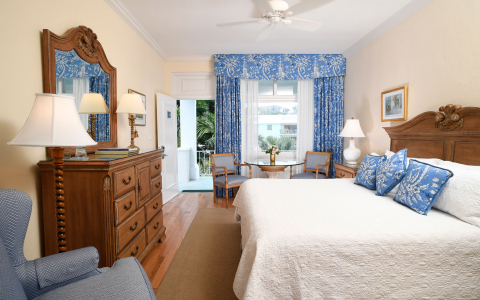 Room with king bed, wooden dresser & light blue accents on pillows & curtains