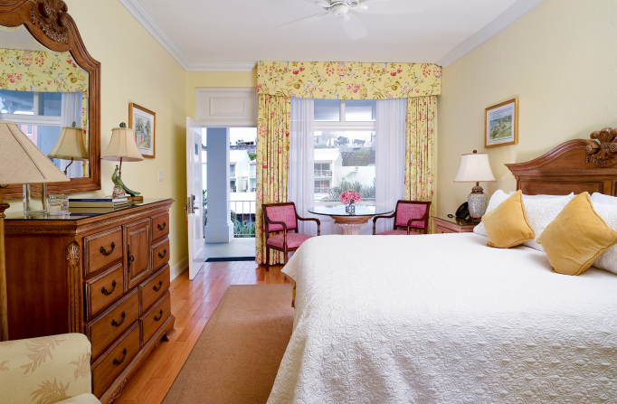 Room with king bed, wooden dresser, seating area with pink chairs next to balcony