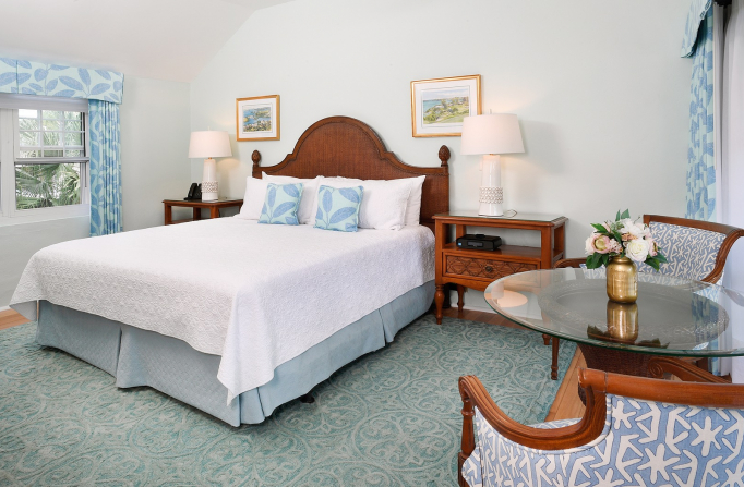 Room with double bed, white sheets & light blue patterned pillows & curtains