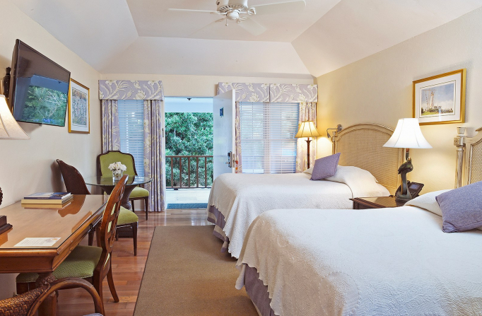 Room with two double beds, wooden desk with chair, seating area & open balcony door