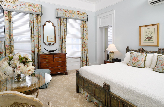Room with king bed, seating area with glass table, & wooden dresser in between two windows