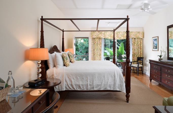Room with king bed, wooden bed frame, nightstands & large window with yellow curtains
