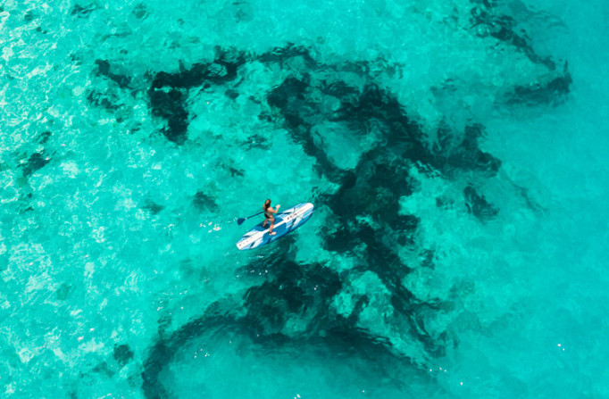 woman paddleboarding in clear blue water