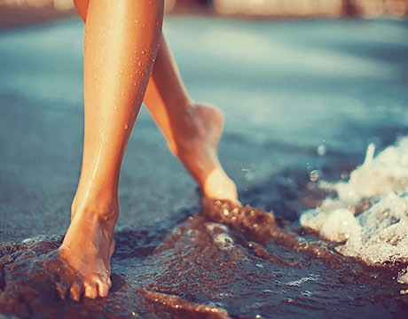 Close up of woman's feet walking in wet sand next to water