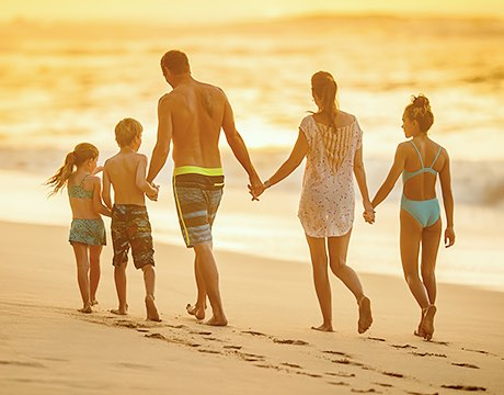 Family of five holding hands walking on the beach at sunset