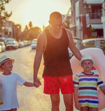 Man walking in street at sunset holding hands with two young children