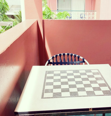 Chair and table in corner of restaurant with chess board on table