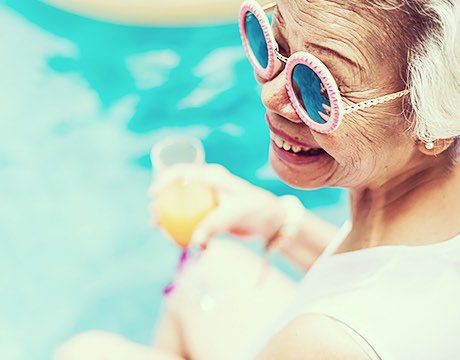 Woman sitting next to the pool wearing sunglasses and holding a cocktail