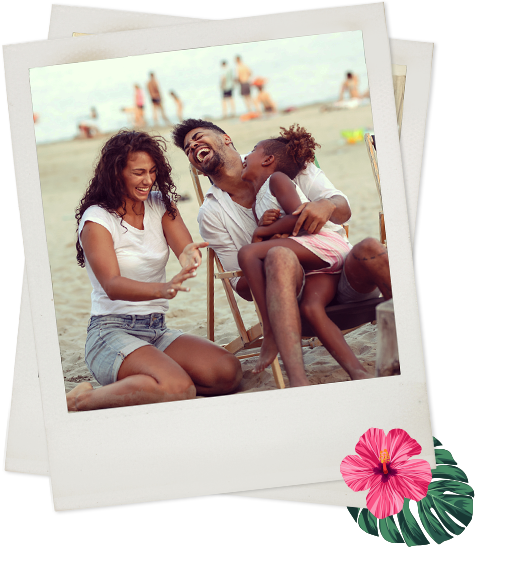Polaroid of a man, woman, and girl sitting on the beach laughing