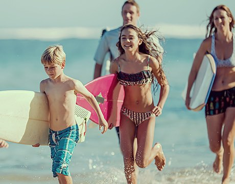 Family running back to the beach with surfboards in hand