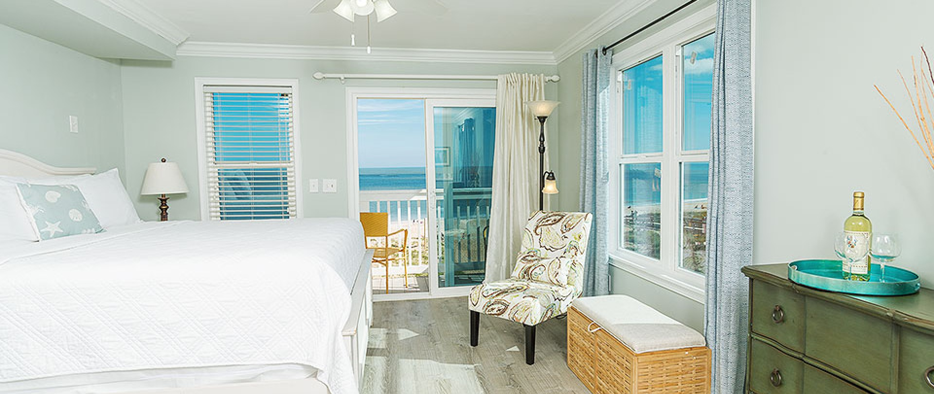 Room with king bed, dresser and chair next to window with ocean view (tablet version)