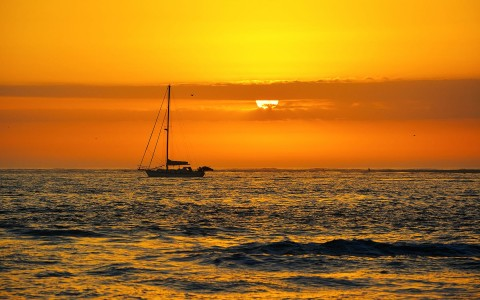 Sailboat moving by with sun rising in the back