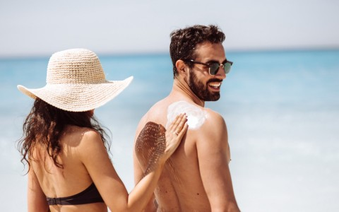 woman rubbing sunscreen on man's back