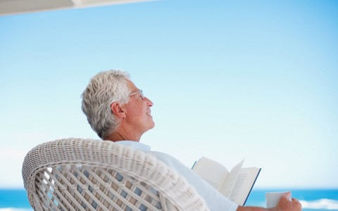 grey haired man relaxing in a wicker chair reading a book